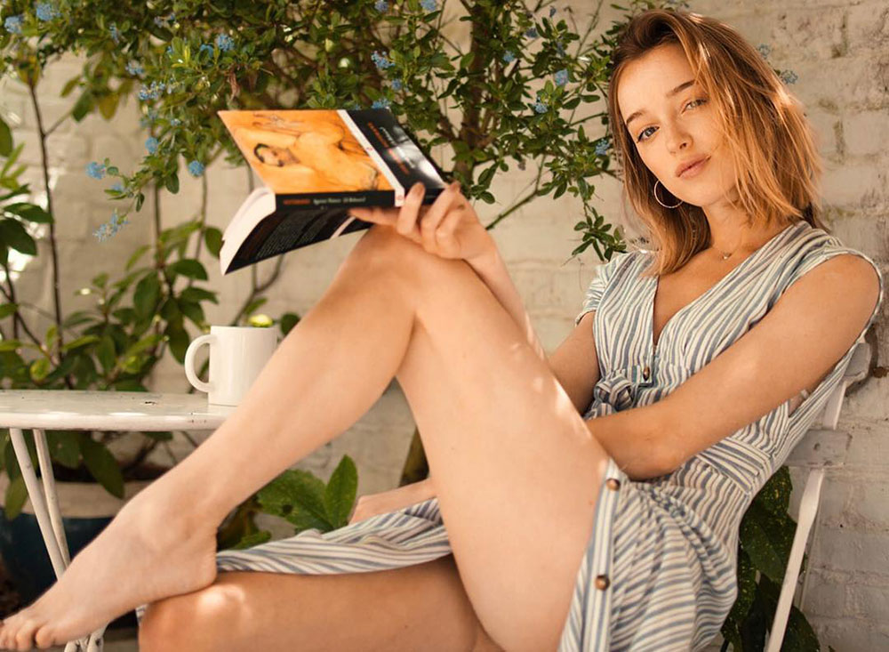 Phoebe Dynevor reading book in shorts