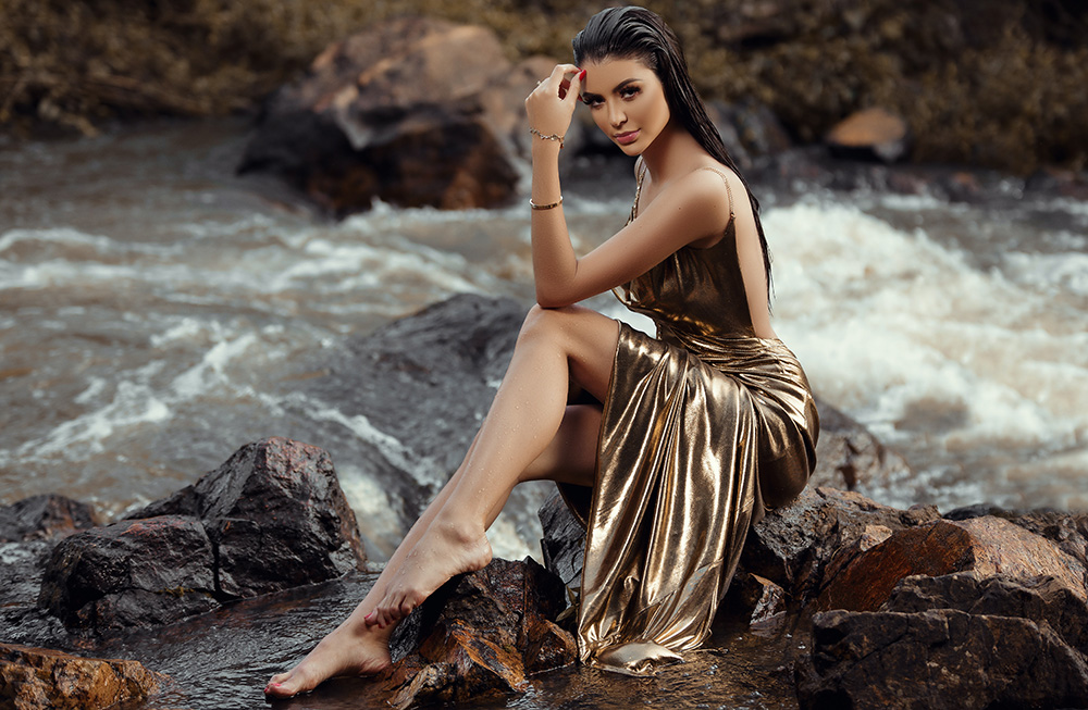 Glamour Model in golden dress by the water stream